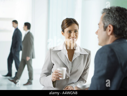 Business colleagues having coffee break in lobby - Stock Photo