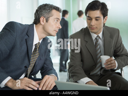Two businessmen sitting around laptop, one with coffee cup - Stock Photo