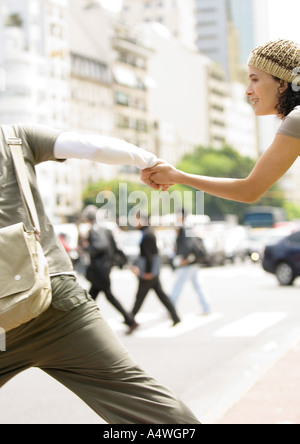 Young couple holding hands, running across street - Stock Photo