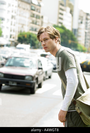Young man standing next to busy street - Stock Photo
