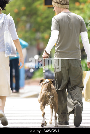 Young couple with dog crossing street - Stock Photo