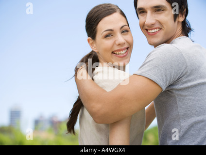 Young couple looking over shoulders, smiling - Stock Photo