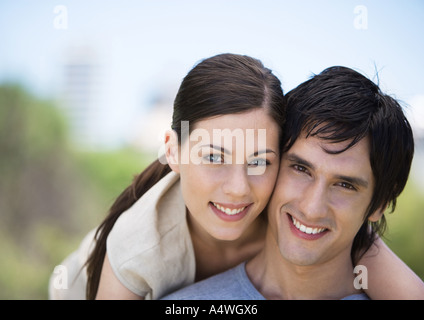 Young couple smiling, cheek to cheek - Stock Photo