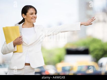 Young businesswoman hailing taxi - Stock Photo