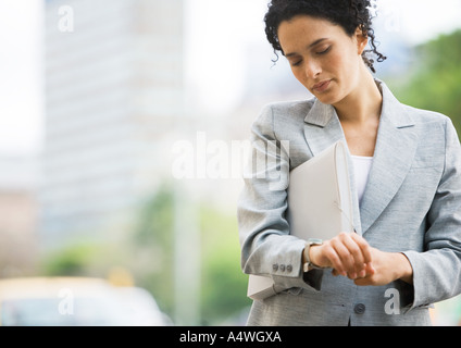 Businesswoman checking watch - Stock Photo