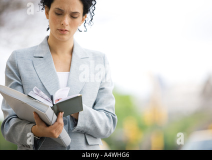 Businesswoman looking down at agenda - Stock Photo
