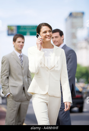 Young businesswoman walking and using cellphone while two businessmen watch in background - Stock Photo