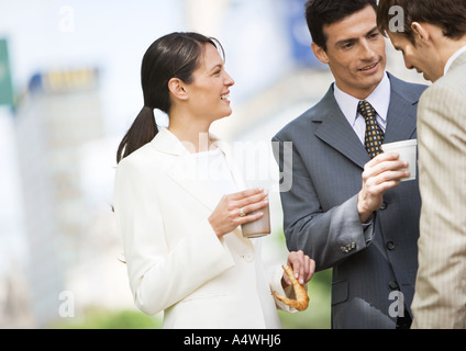 Business colleagues having coffee outdoors - Stock Photo