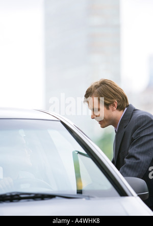 Businessman next to car, speaking to driver - Stock Photo