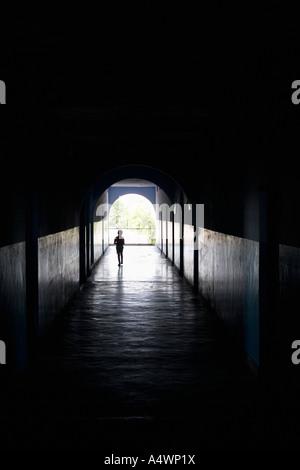 Child walking through a dark hallway - Stock Photo