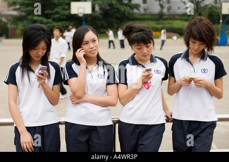 Female students using their cell phones - Stock Photo