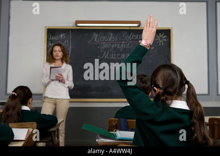 Young student raising her hand in class - Stock Photo