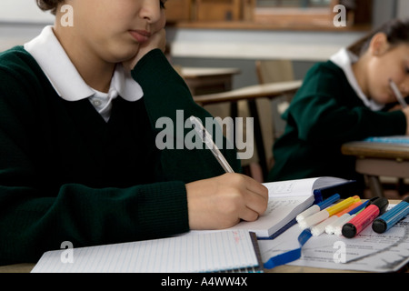 Young student taking notes in class - Stock Photo