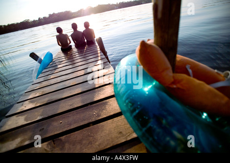 Kids sitting on a dock into a Lake - Stock Photo