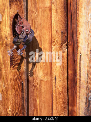 Spurs hanging on a nail on cabin wall Montana - Stock Photo