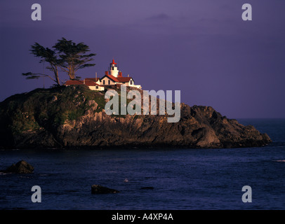 Battery Point Lighthouse on a tidal island shines in a ray of light while fog bank moves in Crescent City California - Stock Photo