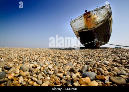 Old fishing boat on shingle beach at Dunwich Suffolk England UK - Stock Photo