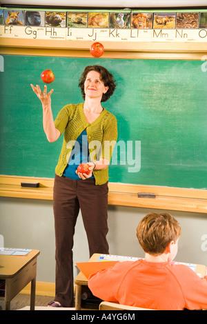 Female teacher juggling apples in classroom - Stock Photo