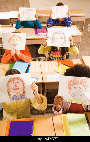 Students holding drawings over faces in classroom - Stock Photo