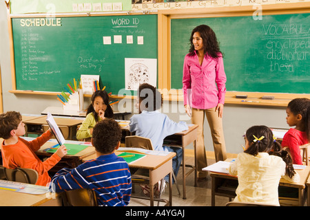 Student holding up work in classroom - Stock Photo