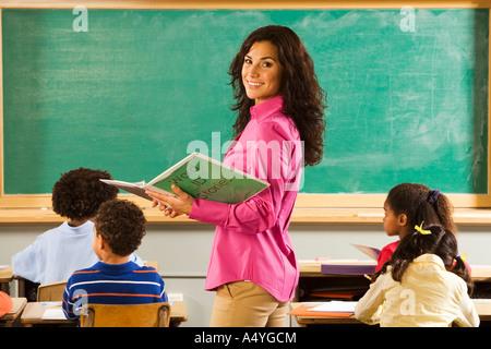 Portrait of female teacher in classroom - Stock Photo