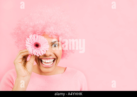 Woman wearing pink wig and holding flower over eye - Stock Photo