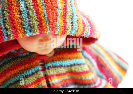 Baby girl in colourful fleece hooded poncho against a white
