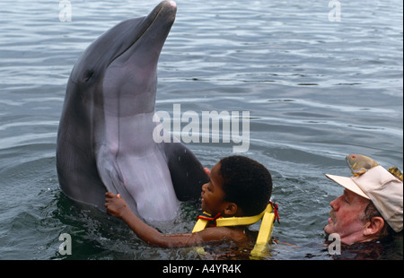 A disabled boy swims with a dolphin at the Dolphin Research Centre in Florida, USA. - Stock Photo