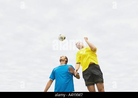 Footballers heading the ball - Stock Photo