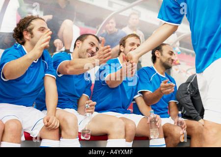 Team congratulating footballer - Stock Photo