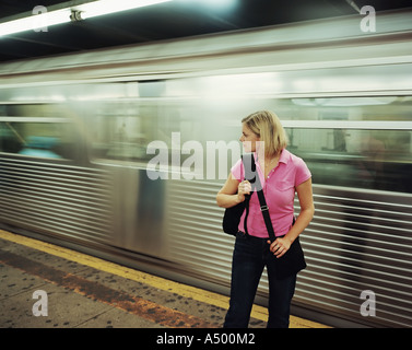 Woman on platform while train speeds by - Stock Photo