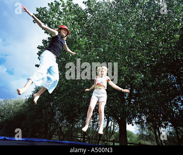 Two girls jumping on trampoline - Stock Photo