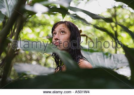 Young woman through foliage - Stock Photo
