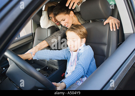 Boy trying to drive parents' car - Stock Photo