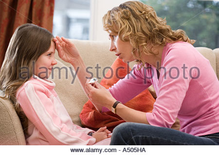 Mother taking daughter's temperature - Stock Photo