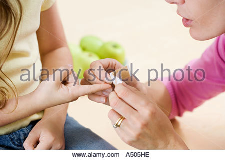 Woman putting plaster on daughter's finger - Stock Photo