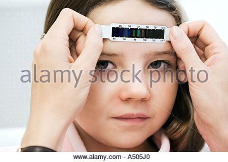 Girl having her temperature taken - Stock Photo