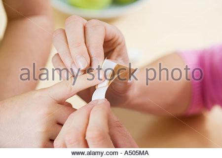 Mother putting plaster on child's finger - Stock Photo