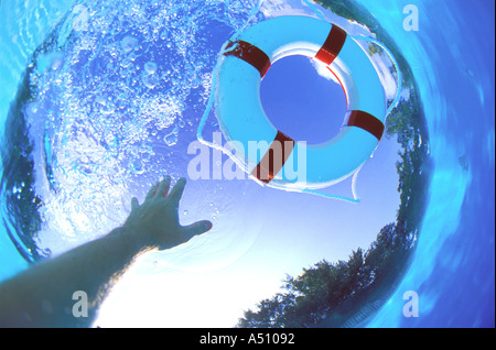 Swimmers hand reaching up toward life saving ring floating on surface of water - Stock Photo