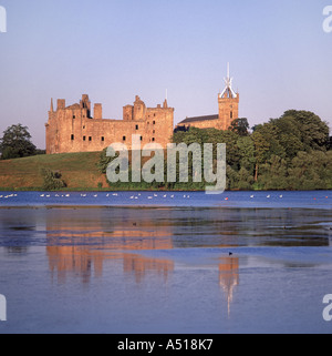 Linlithgow Loch the ruined Palace with the tower of St Michaels Church beyond - Stock Photo