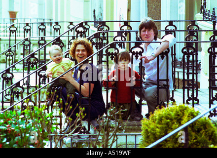 Mother father and two young sons sit outside on steps in the front of their period home with iron railings - Stock Photo