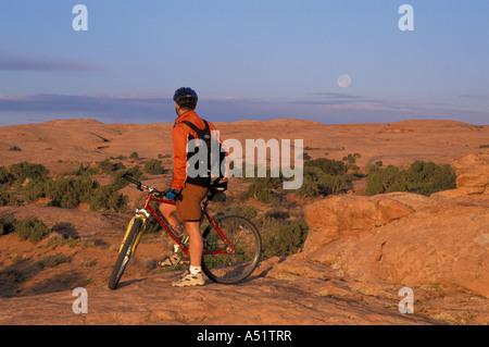 Moab UT Mountain biking on the Moab Slickrock Bike Trail Navajo Sandstone BLM land Full moon - Stock Photo