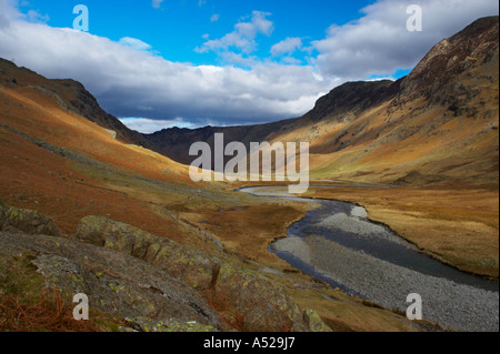 England, Cumbria, Lake District National Park. Brief shafts of sun illuminate the surrounding peaks of the Langstrath - Stock Photo