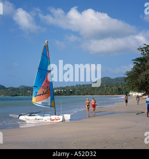 Double hulled Hobie Cat Catamaran at waters edge of Choc Beach couple walking West Coast St Lucia The Caribbean - Stock Photo