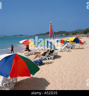People sunbathing under colourful sun brollies on Reduit Beach with Rodney Bay beyond north west coast St Lucia - Stock Photo