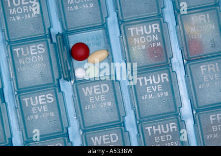 An elderly senior citizen person's daily weekly pill organizer - Stock Photo
