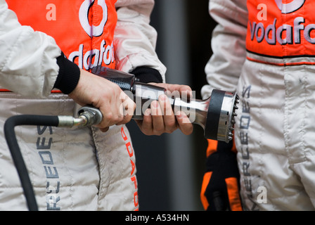 McLaren mechanic holds speed driver used to unscrew wheel lug nuts - Stock Photo