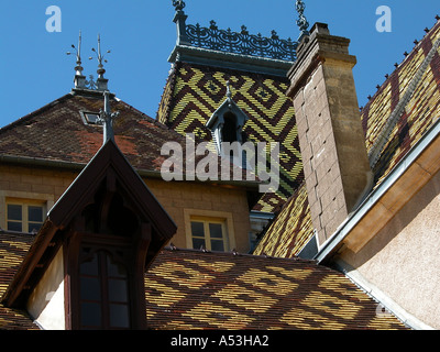 Decorative traditional glazed tiled geometric patterned roof of a Chateau in Burgundy France - Stock Photo