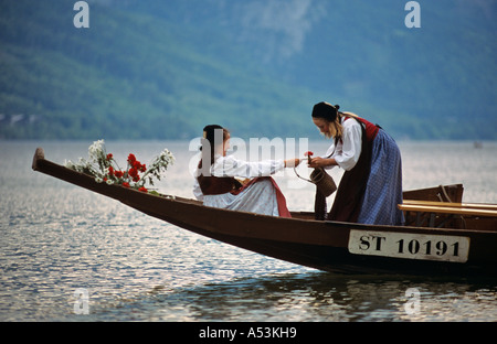 Young girls in a wooden boat traditional daffodil festival on the Grundl lake Styria Austria - Stock Photo