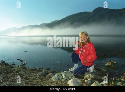 A girl is brushing teeth at the Teletskoye Lake coast Altai Siberia Russia